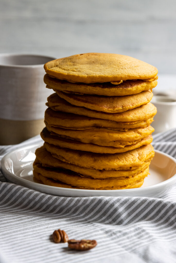 Pumpkin Pancakes stacked on a white plate