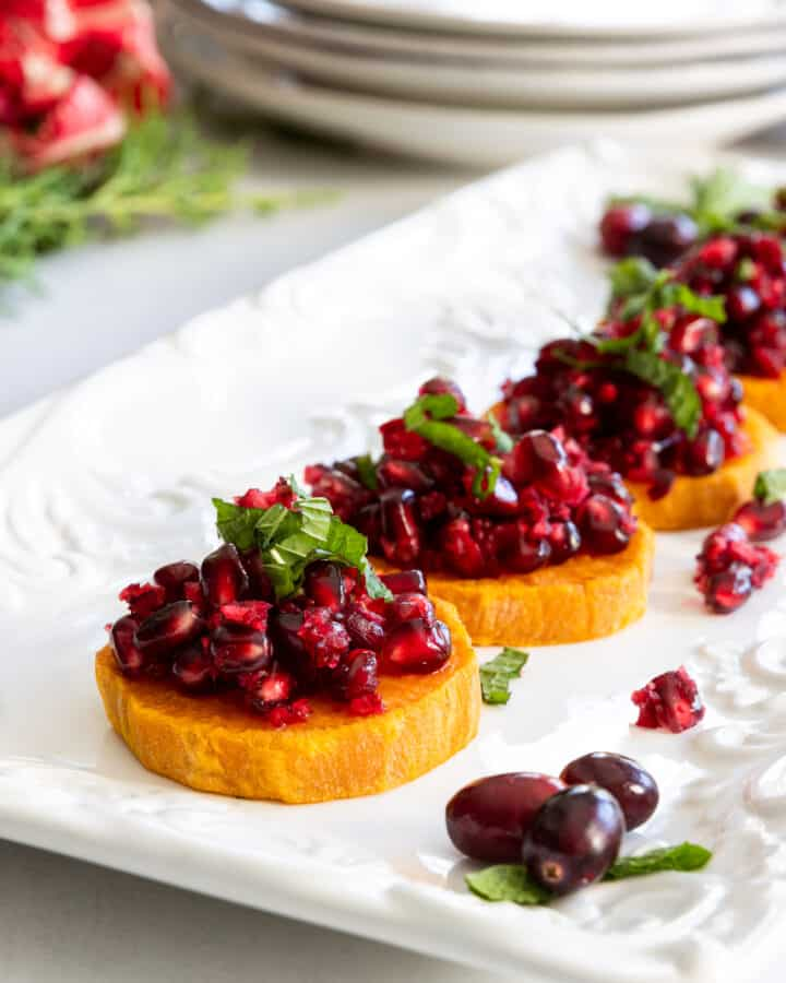 Roasted Sweet Potato Slices with Fresh Cranberry and Pomegranate Relish Served on a White Plate