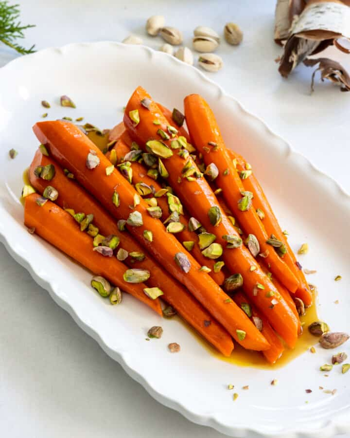 Roasted Carrots with Spicy Maple Glaze and Pistachios on a White Platter