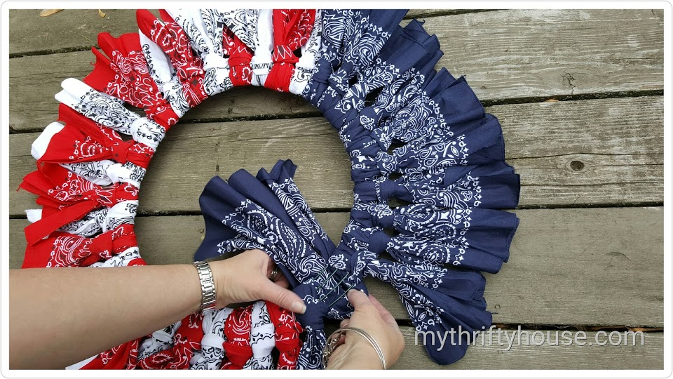Tying and knotting fabric around wire wreath to make a patriotic bandana wreath
