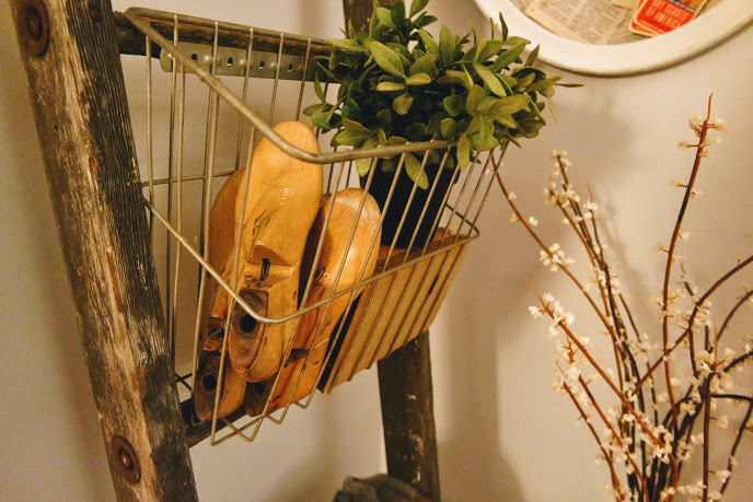 Rustic ladder with vintage wire baskets and faux plant