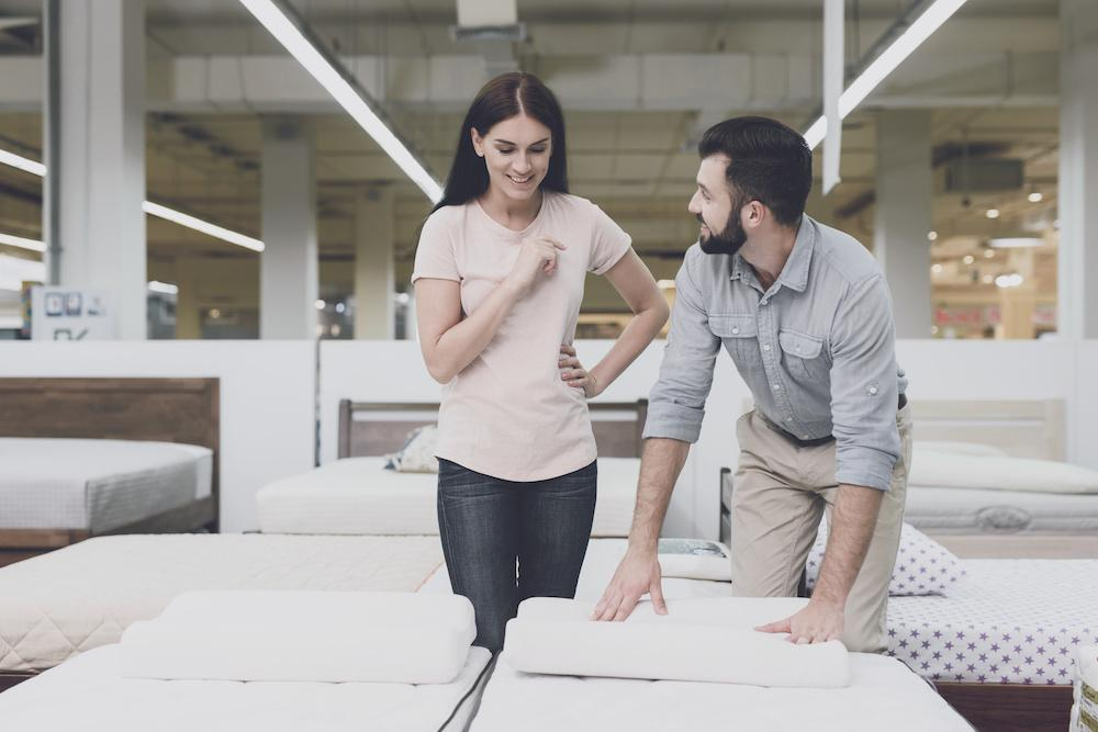 A couple in a large store inspects the mattress before buying. They stand next to him and study him