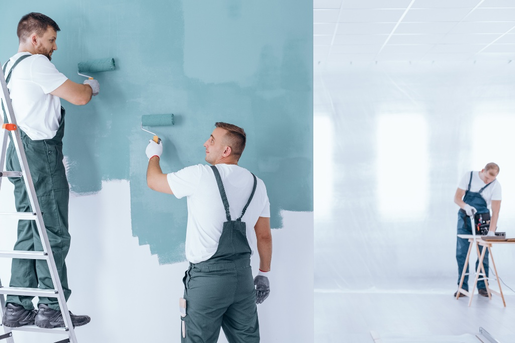 Men painting the wall blue using rollers in empty home interior