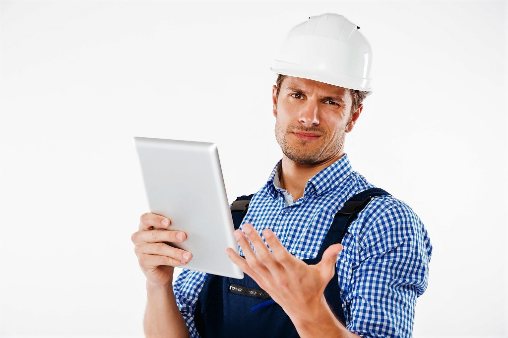 Confused builder in helmet scratching his head and holding tablet