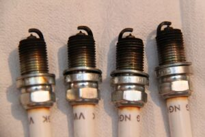 Image Of Four Used Spark Plugs With Black Tips