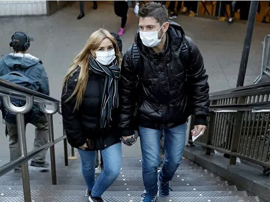 People emerge from the subway wearing protective face masks at Columbus Circle in New York City. Peter Foley/EPA-EFE/Shutterstock