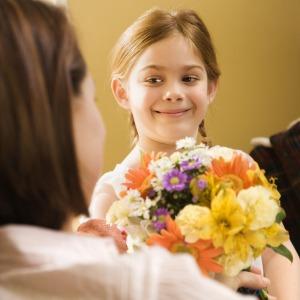 Girl giving mom flowers.