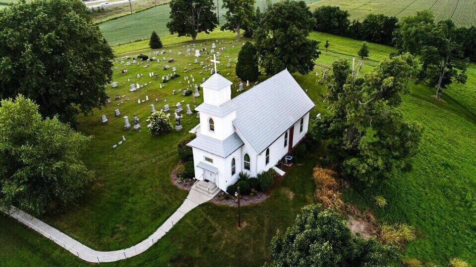 drone shot of a white church in Ohio surrounded by a cemetery