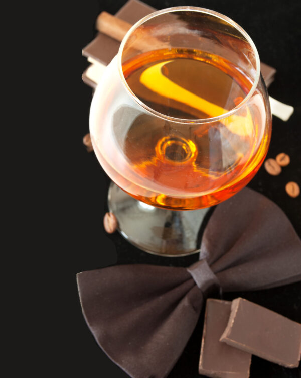 Brandy, cigar, chocolate and coffee beans and bow tie