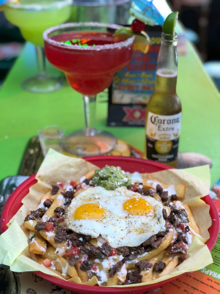 Fiesta Fries with carne asada steak and 2 fried eggs on top, Mega Margarita, Corona