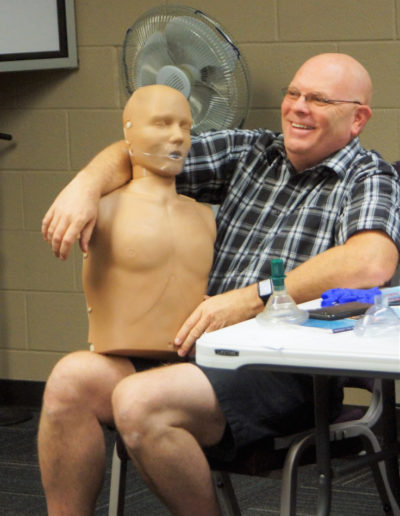 Photo of a man holding a training manikin