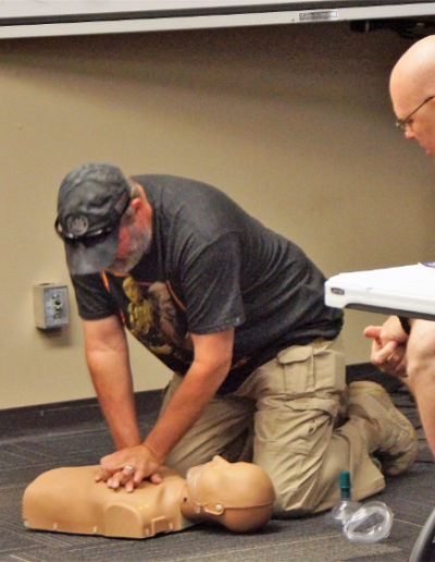 Picture of a student practicing chest compressions on an adult manikin