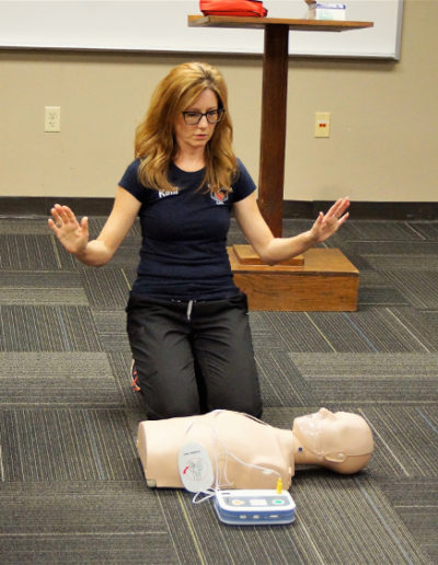 "Photo of instructor demonstrating AED training - how to get into the ""all clear"" poise."