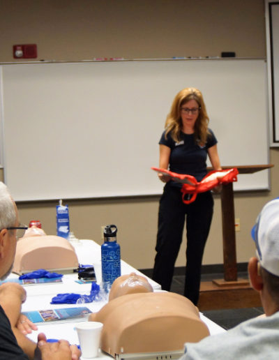 Photo of instructor showing first aid kit contents