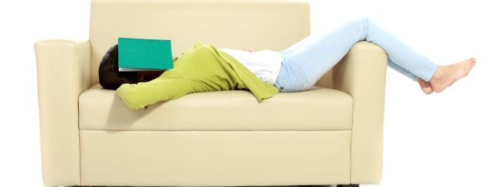 Tired young female sleeping on sofa