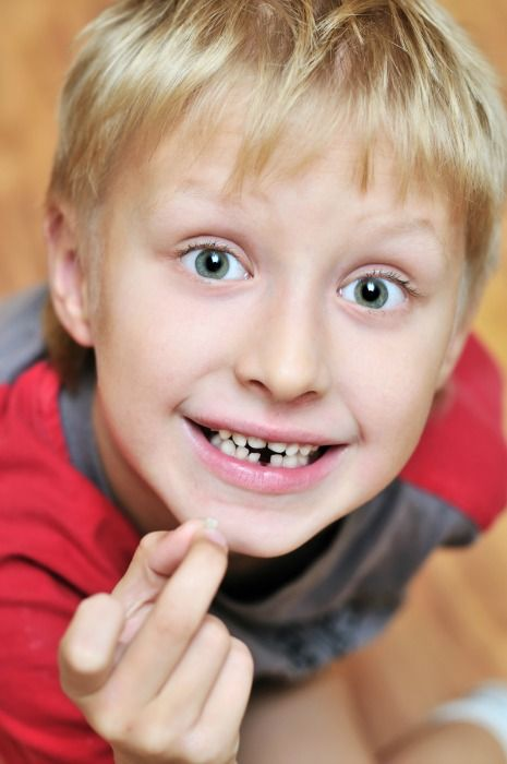 Child with lost tooth in hand