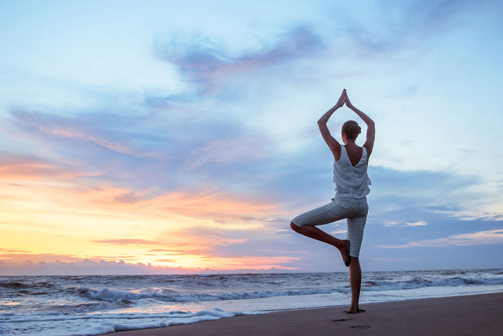 A woman doing a yoga pose at the beach