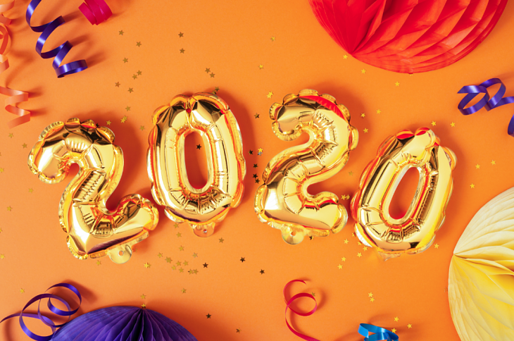 "The number ""2020"" etched out in balloons with party streamers and confetti in the background"