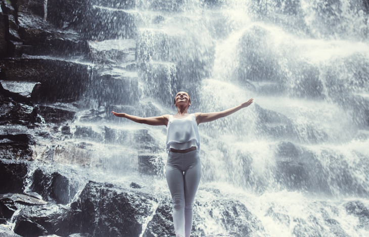Woman posing in front of a waterfall