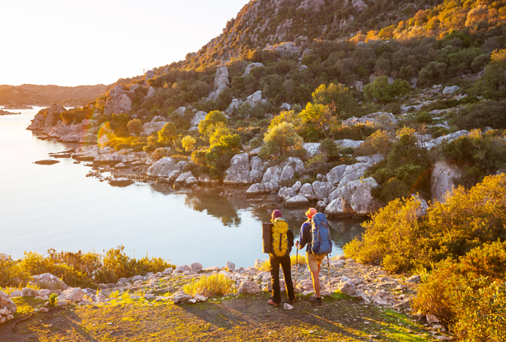 Two hikers on a cliff looking at a body of water