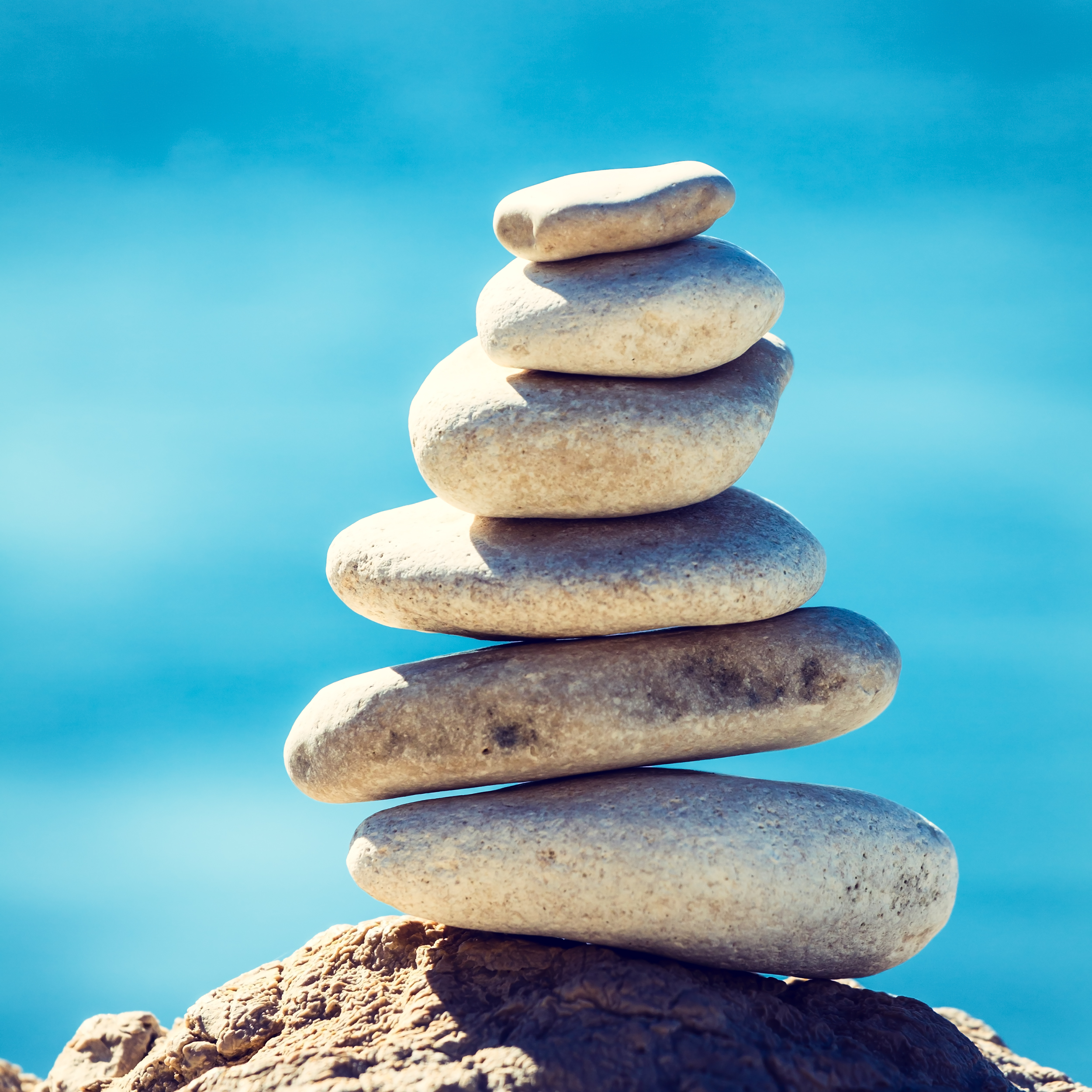 Six gray rocks stacked together with a blue background