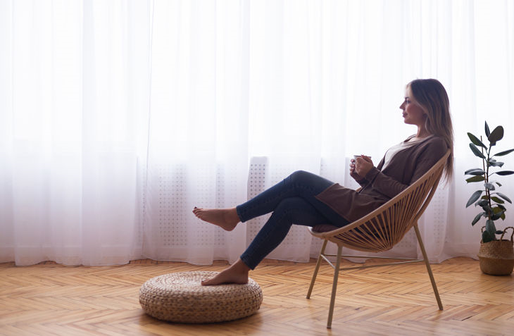 Woman sitting on chair drinking coffee
