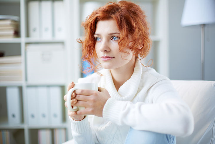 A woman looking concerned while holding a cup of coffee