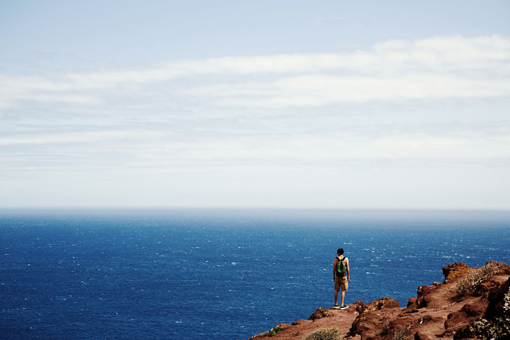 Man standing on cliff looking at ocean