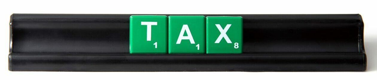 Green tiles on a black holder spelling the word Tax on the Pro Tax & Accounting Frequently Asked Questions page