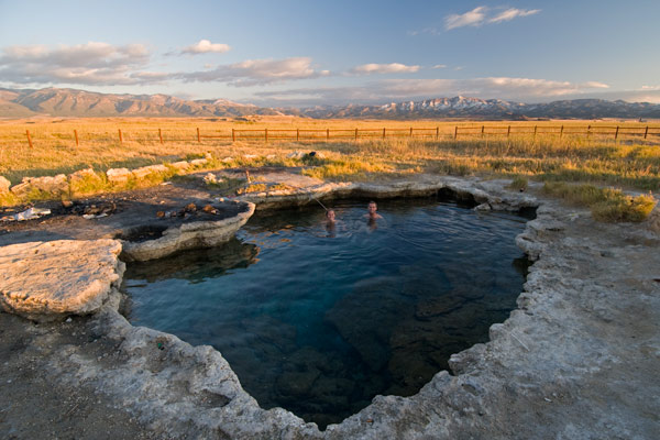 Two people enjoy one of the hot springs, which sits in the middle of a golden field surrounded by mountains.