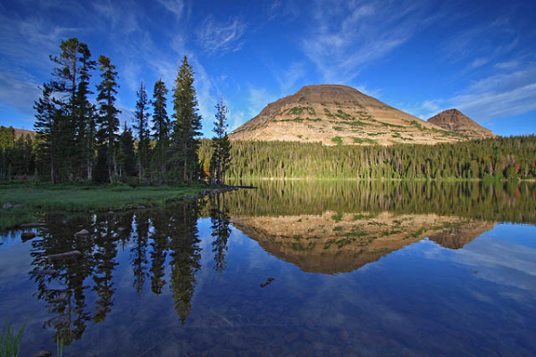Mountain perfectly reflected in Mirror Lake. The sky is blue with scattered cirrus clouds, and the sun shines directly on the peak.