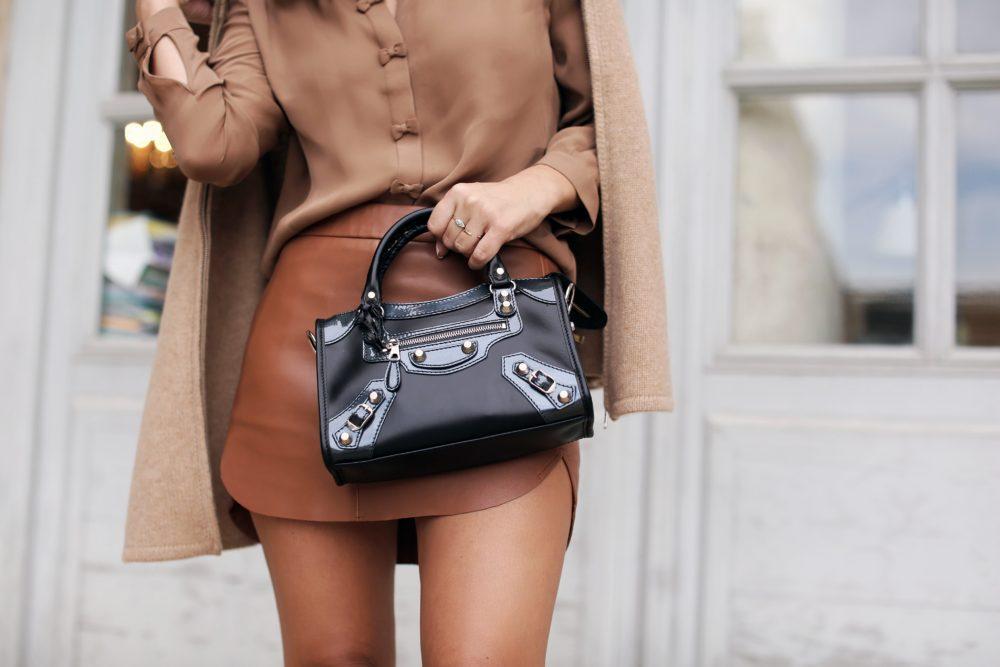 marianna hewitt outfit paris fashion week tan leather skirt balenciaga bag tan cape