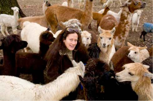 Angel Forbes-Simmons poses with her beloved alpaca and llama herd