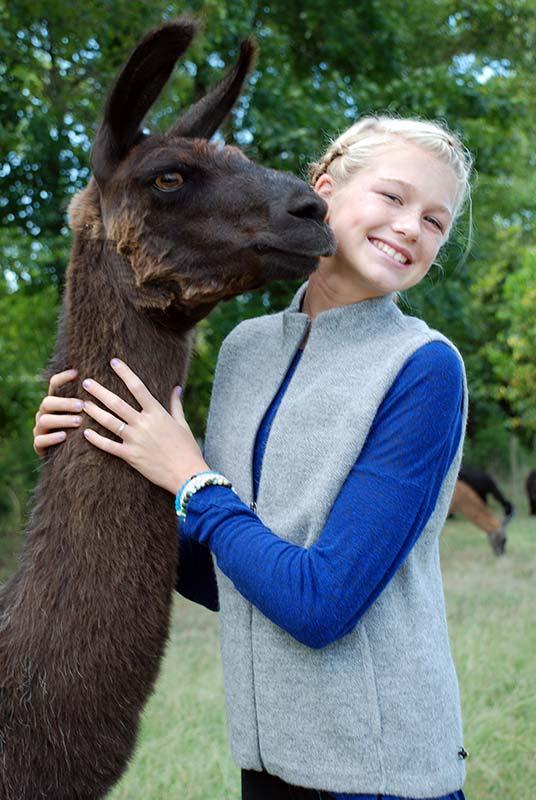Girl modeling grey alpaca vest with llama