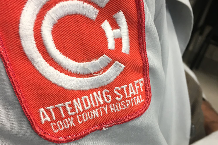 closeup of a red & white patch on a white coat; Attending Staff, Cook County Hospital
