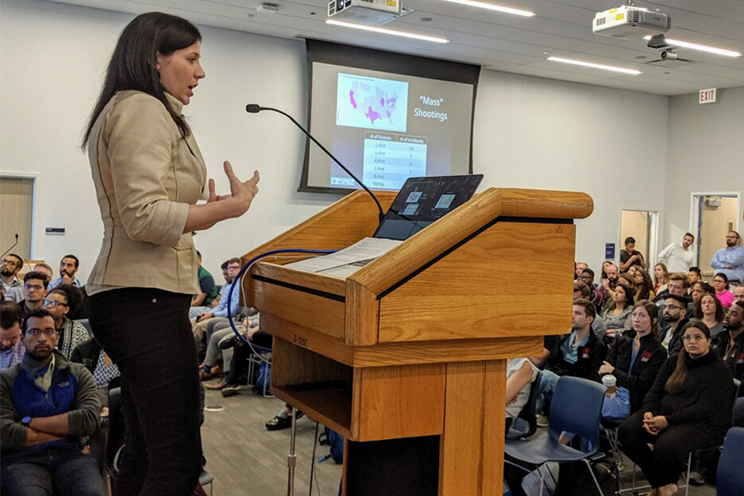 woman standing in front of a wooden podium, lecturing to a group of people; projection screen on wall in background