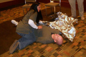 woman kneeling on carpeted floor next to bald man pretending to be injured; she is reaching for a foil covering