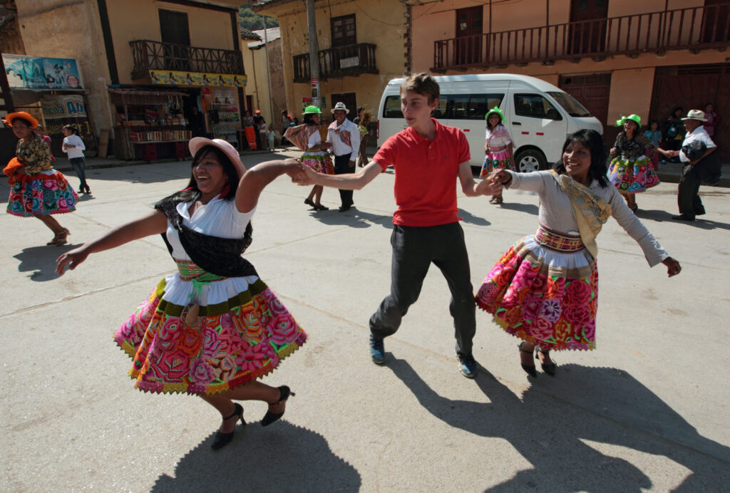 Alex Chmielinski, 15, dances with local residents of Izcuchaca, Peru as they celebrate the Feast Day of their patron saint Santiago in their town square.  Alex is the son of Amazon River explorer Piotr Chmielsinki who is helping guide the Amazon Express team to a possible new source of the Amazon River high in the Andes mountains of Peru.   Amazon Express expedition in Peru August 11, 2012.    Photo by Erich Schlegel