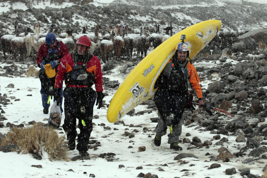 Amazon Express white water team members John Maika (Austin, TX), left, Rafael Ortiz (Mexico), right,  and expedition leader West Hansen (Austin, TX) , back, portage their kayaks around a llama pen during a snow storm shortly after the start of white water kayaking out of Lago Acucocha.  Amazon Express expedition at Lago Acucocha near Alpamarca, Peru August 18, 2012.    Photo by Erich Schlegel