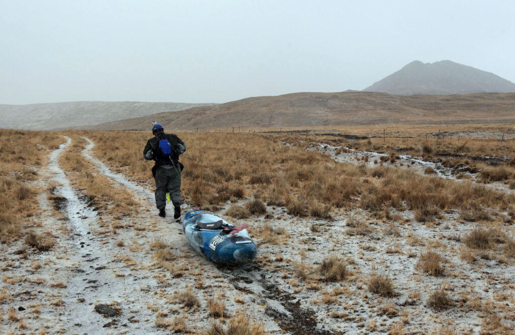 Due to low water, Amazon Express expedition leader West Hansen (Austin, TX) drags his white water kayak down a ranch road along the Rio Gachon for several miles.  Amazon Express expedition on Rio between Alpamarca and San Pedro de Racco, Peru August 19, 2012.    Photo by Erich Schlegel
