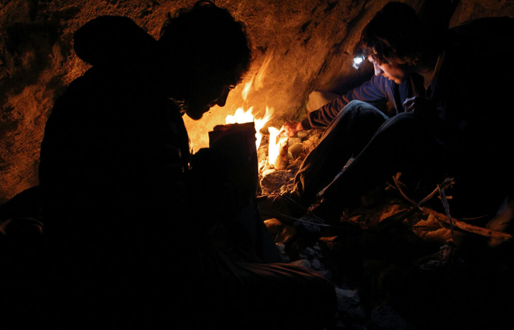 Amazon Express white water team members Tino Specht (USA), left, and Simon Yerovi (Chile) heat up their freeze-dried dinners beside the campfire on the first white water overnight campsite on the Rio Mantaro.  Amazon Express expedition in Peru August 20, 2012.    Photo by Erich Schlegel