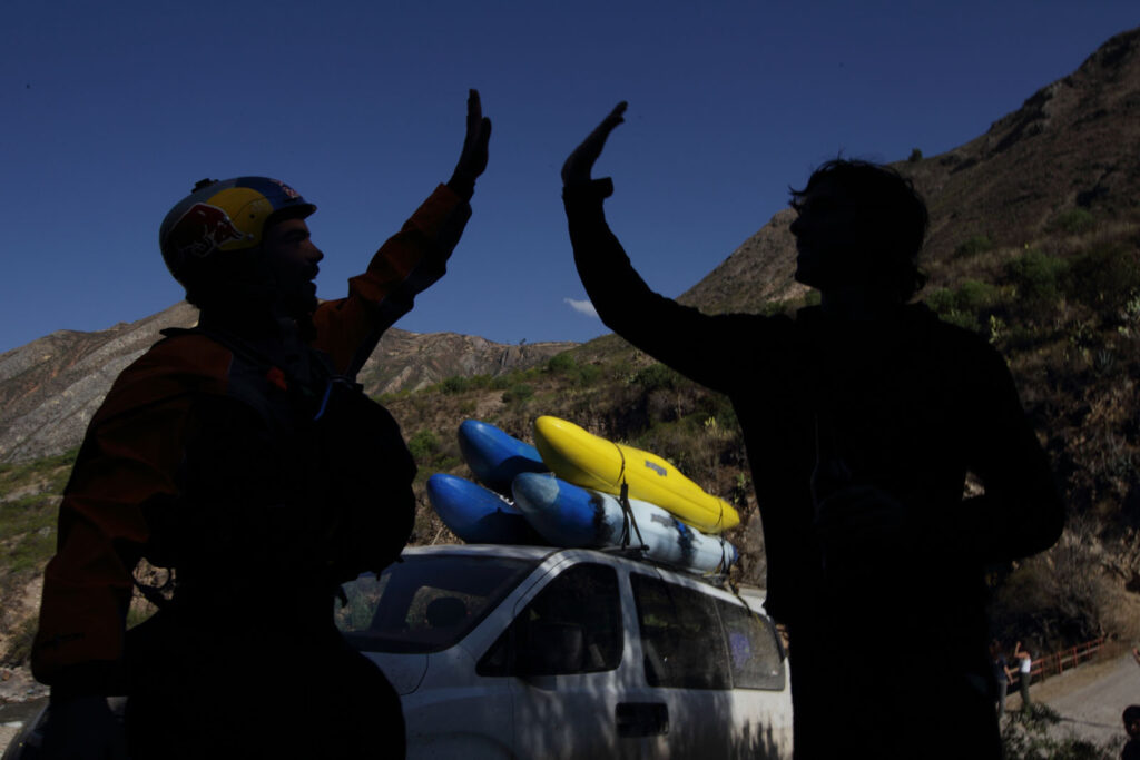 "Amazon Express white water team members Rafael Ortiz (Mexico) and Simon Yorovi (Chile) ""high five"" after negotiating the Rio Mantaro near Moya, Peru,  Amazon Express expedition in Peru August 17, 2012.    Photo by Erich Schlegel"