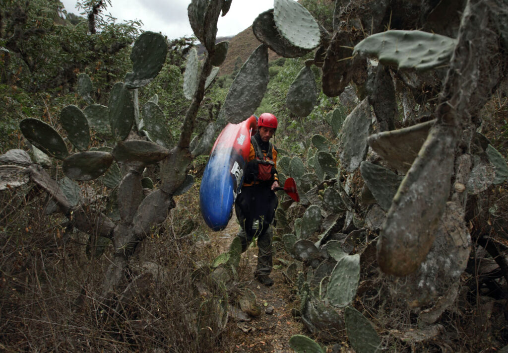 Amazon Express white water team member Simon Yerovi (Chile) carries his kayak through a cactus field up from the Rio Mantaro. Yerovi was feeling very ill from the contaminated river water. Two other white water members also became ill that night.  Amazon Express expedition in the Mantaro River downstream from Izcuchaca, Peru August 25, 2012.    Photo by Erich Schlegel
