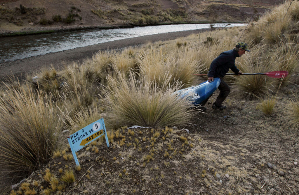 Amazon Express expedition member John Maika hauls up leader West Hansen's white water kayak after Hansen paddled the Rio Mantaro near Paccha, Peru. The campsite was an abandoned golf course, Club de Gold La Oroya owned by the Doe Run mine company. Doe Run was shut down three years ago after legal action was taken against the company for contaminating the Rio Mantaro.  Amazon Express expedition in Peru September 8, 2012.    Photo by Erich Schlegel