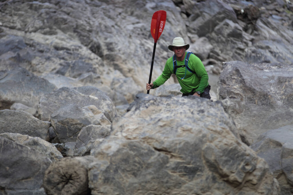 Amazon Express expedition leader West Hansen climbs through boulder fields while negotiating the Rio Manraro below Tablachaca Dam. The water is very low in this section of river during Peru's dry season. Water is also low due to the diversion of much of the Rio Mantaro through a tunnel for use in ElectroPeru's largest hydroelectric project downriver.  Amazon Express expedition in Peru September 12, 2012.    Photo by Erich Schlegel