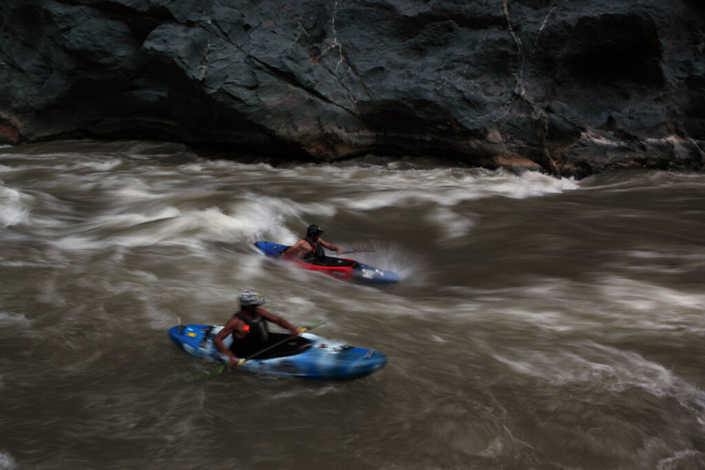 "Amazon Express safety kayakers Daniel Rondon Casos, top, and Siabanel Loayza Carbajal take turns ""surfing"" a wave after stopping for the day in the lower Rio Mantaro canyons.  Amazon Express expedition in Peru September 18, 2012.    Photo by Erich Schlegel"