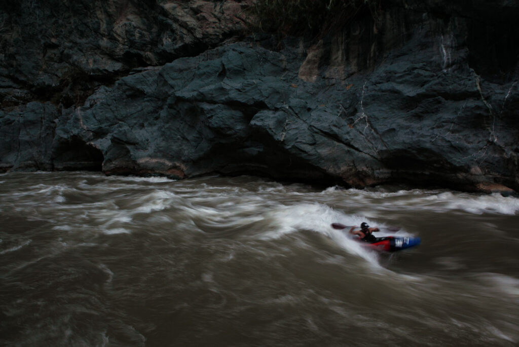 "Amazon Express safety kayakers Daniel Rondon Casos  ""surfs"" a wave after the team stopped for the day in the lower Rio Mantaro canyons.  Amazon Express expedition in Peru September 18, 2012.    Photo by Erich Schlegel"