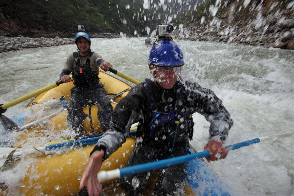 Amazon Express raft guide Juan Antonio de Ugarte of Cuzco, Peru runs expedition leader West Hansen through white water rapids and a splash in the face along the lower Rio Mantaro.  Amazon Express expedition in Peru September 19, 2012.    Photo by Erich Schlegel