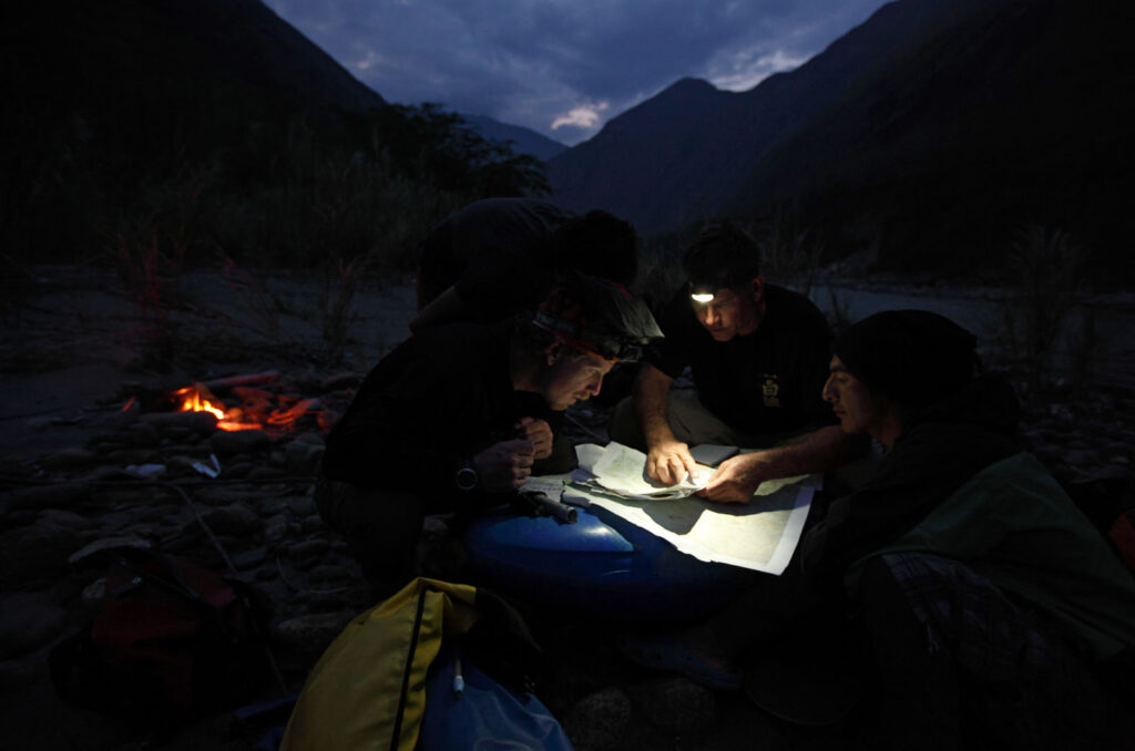 Amazon Express expedition leader West Hansen goes over topographic maps with raft guide Juan Antonio de Ugarte, back left, and white water kayakers Santiago Iba–ez Corpancho, left, and Siabanel Loayza Carbajal, right, at a campsite on the lower Rio Mantaro.  Amazon Express expedition in Peru September 19, 2012.    Photo by Erich Schlegel