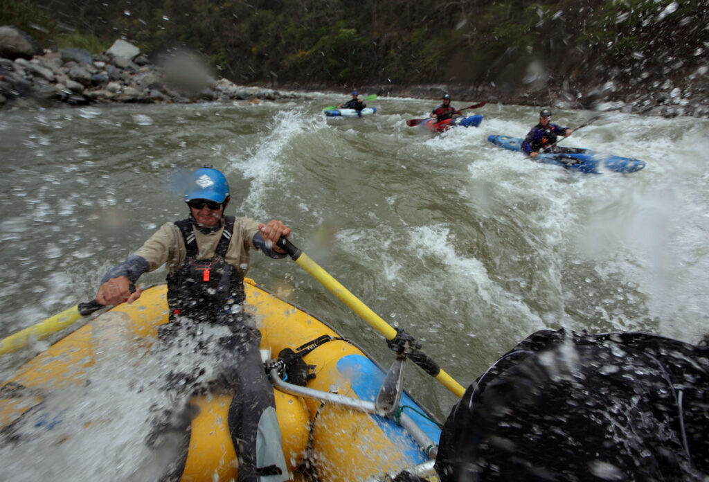 Amazon Express expedition raft guide Juan Antonio de Ugarte of Cuzco, Peru guides the raft through rapids on the lower Rio Mantaro as white water kayakers follow. From back left, expedition leader West Hansen, Daniel Rondon Casos, and Santiago Iba–ez Corpancho.  Amazon Express expedition in Peru September 21, 2012.    Photo by Erich Schlegel